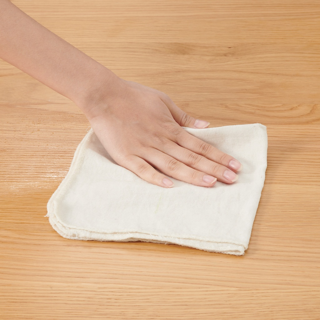 Mão passando pano branco sobre mesa de madeira clara.