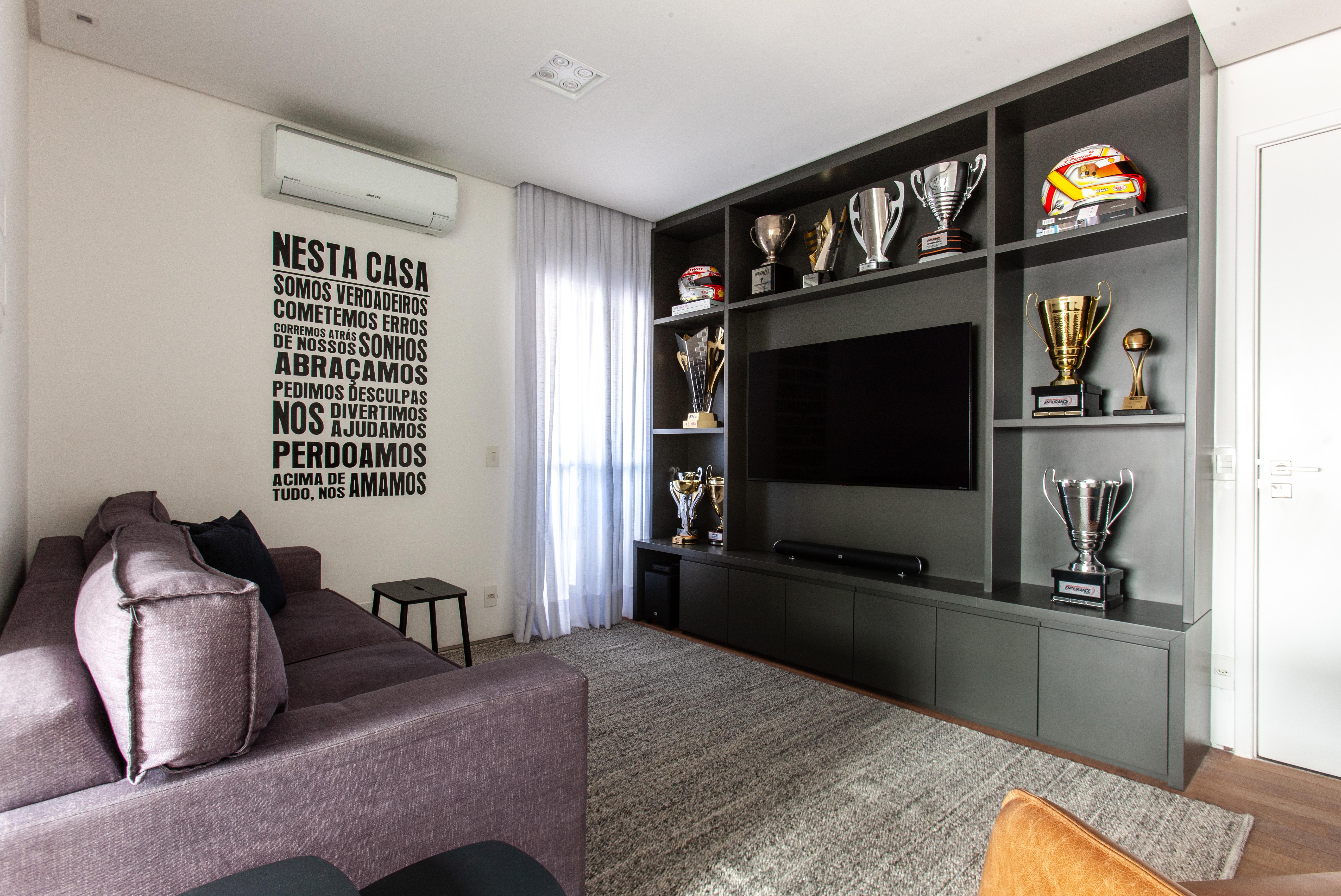 Sala de TV cujo painel é também uma estante que comporta troféus e capacetes de automobilismo