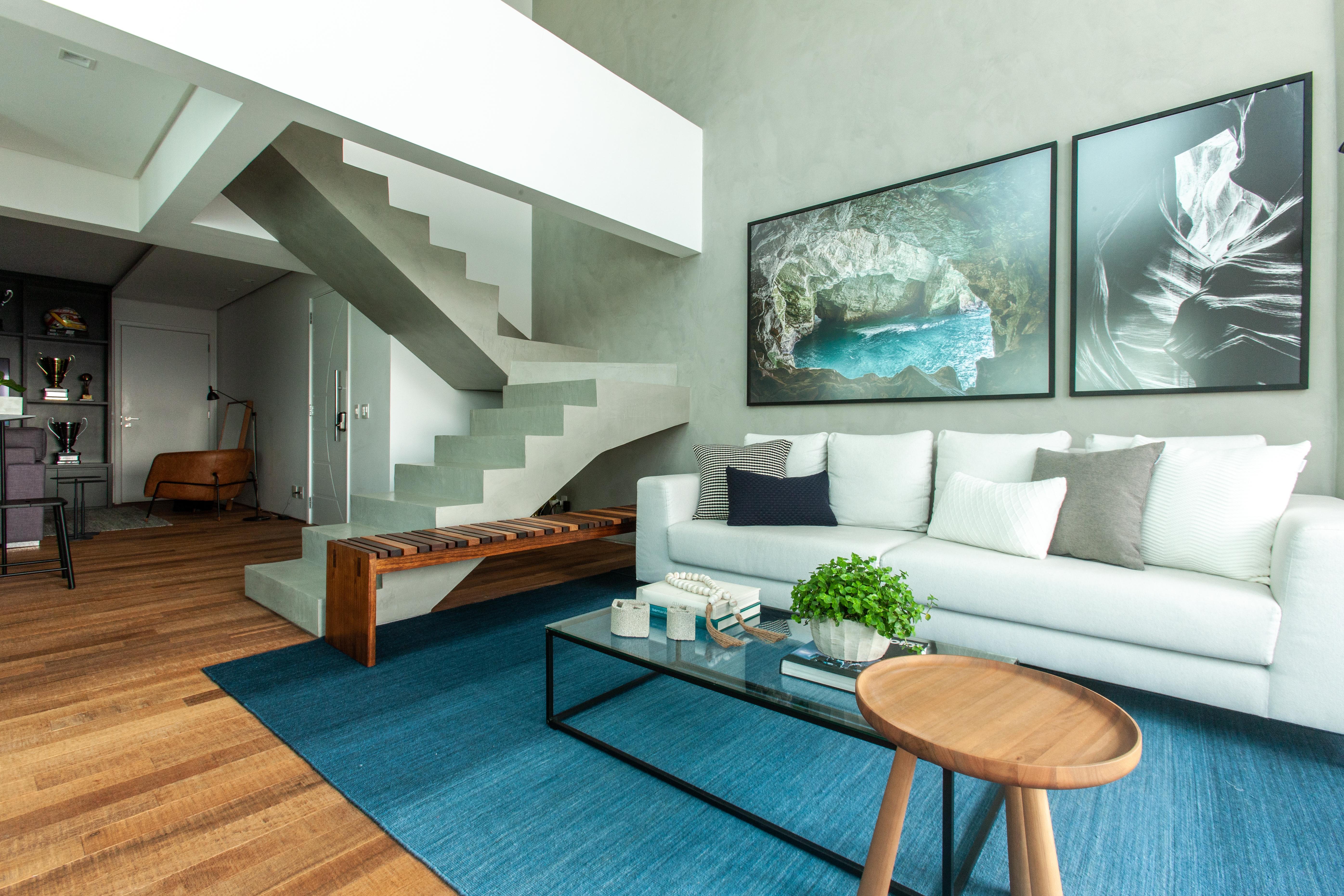 Sala de estar com cimento queimado nas paredes, piso de madeira e escada de cimento