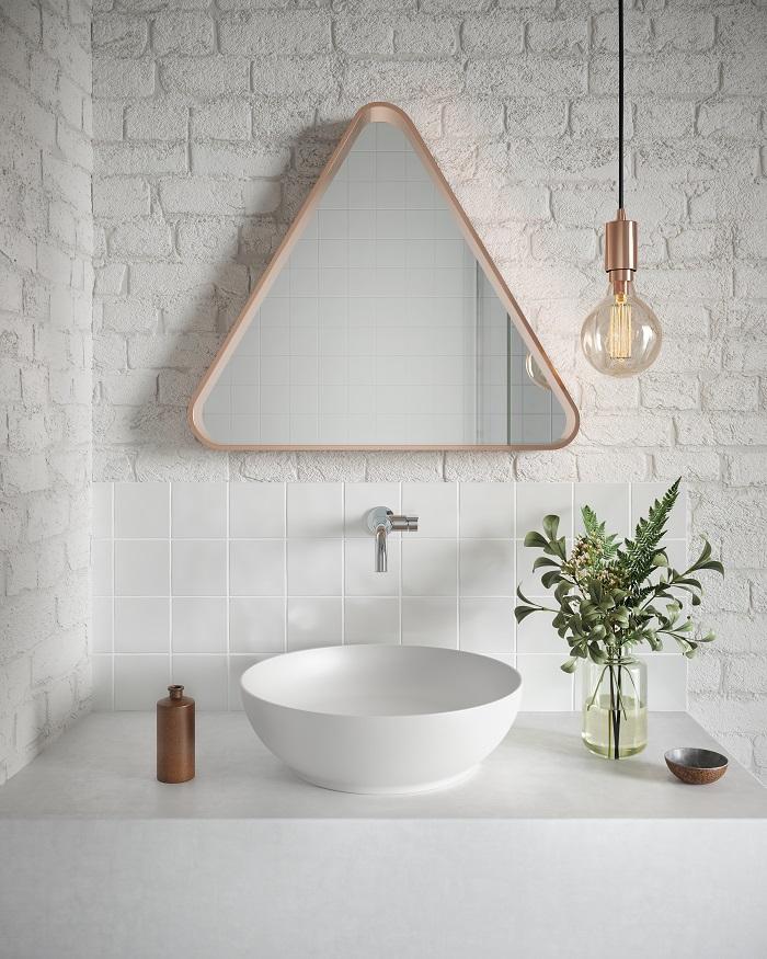 Banheiro minimalista com cuba branca e espelho triangular