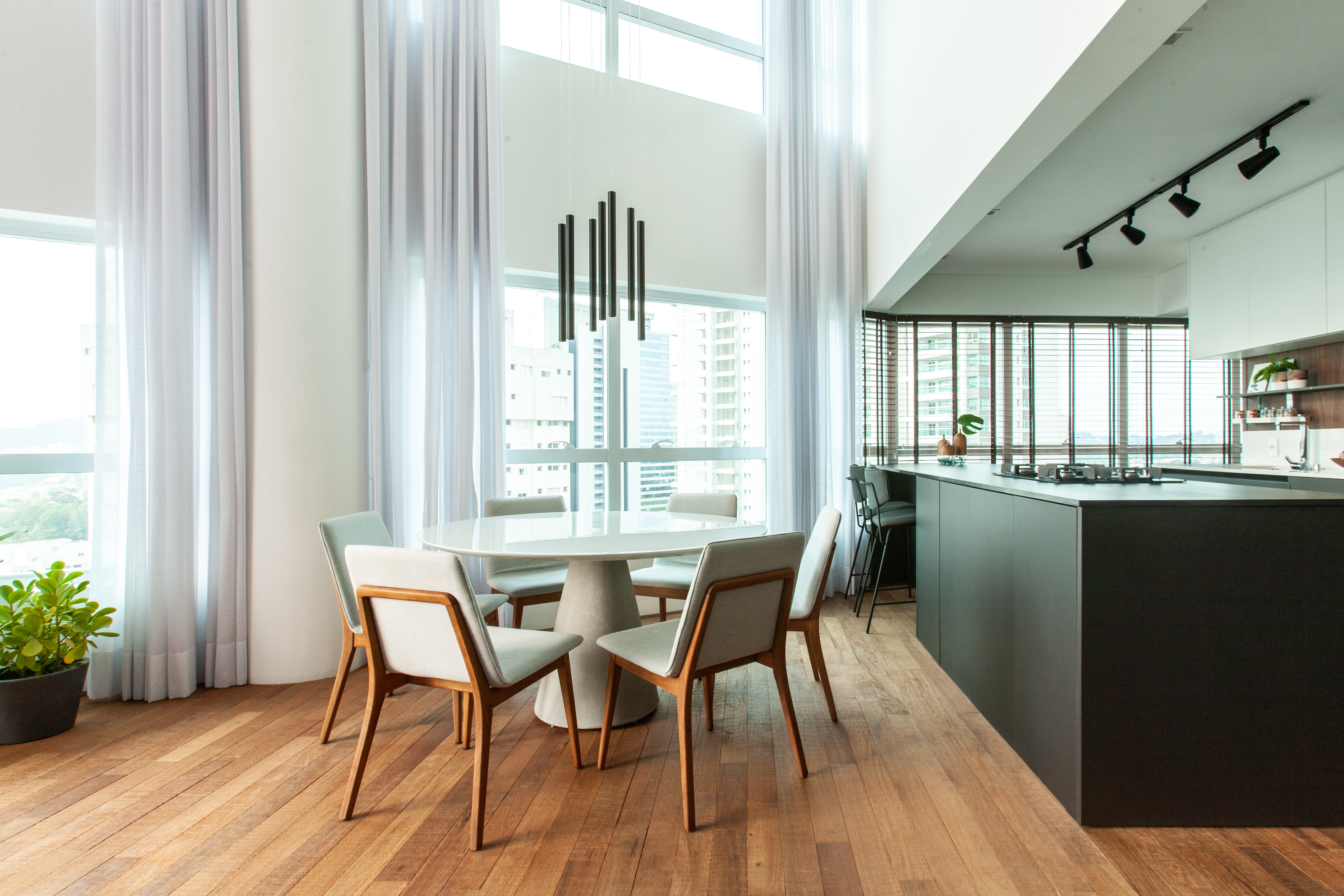 Sala de jantar integrada à cozinha. Pé direito alto, piso de madeira