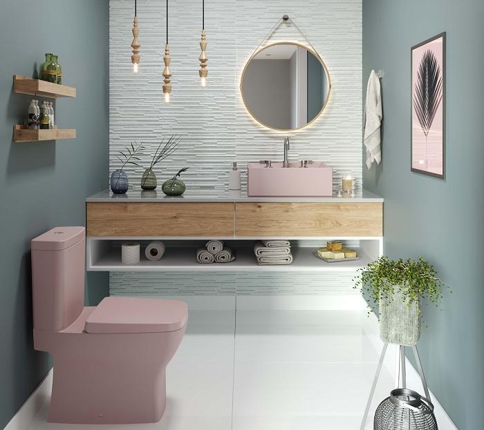 Banheiro com paredes pintadas de azul e verde mint e cuba e bacia rosa
