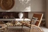 Cadeira e tapete em tons terrosos compões o ambiente, com um compartimento para lenha em parede de cmento queimado com itens de decoração culturais