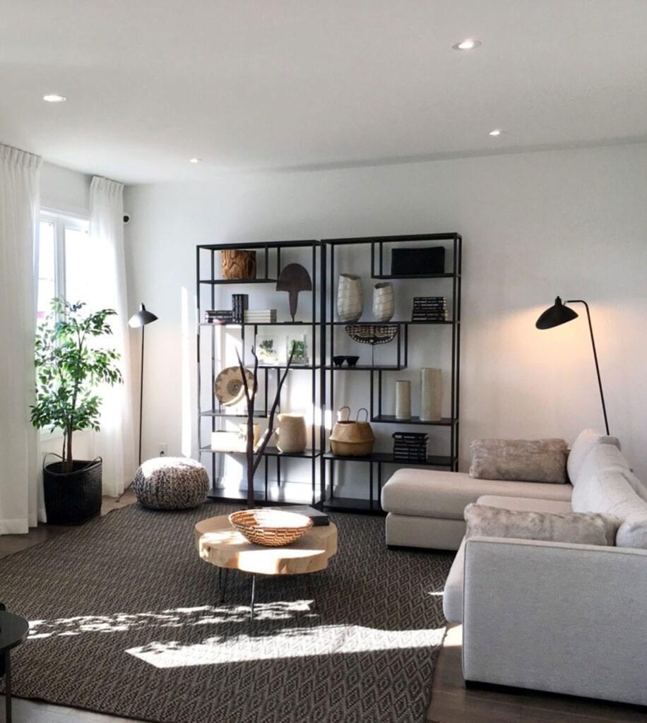 Sala de estar com tapete cinza, mesa de centro e sofá na cor branca e estante com diversos itens decorativos. Uma luminária de chão, junto com uma janela ampla na parede de frente, garante a iluminação do ambiente