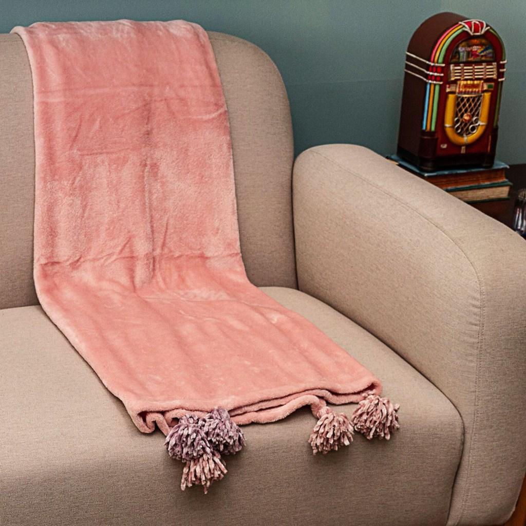 Poltrona bege com manta rosa de veludo sobre elas