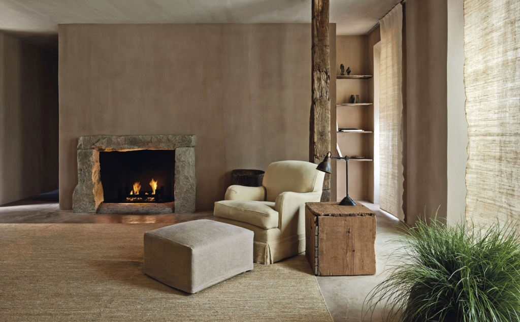 Tons de bege se misturam com tapete, poltrona e parede. Uma lareira ao fundo, para aquecer o ambiente e plantas para decoração