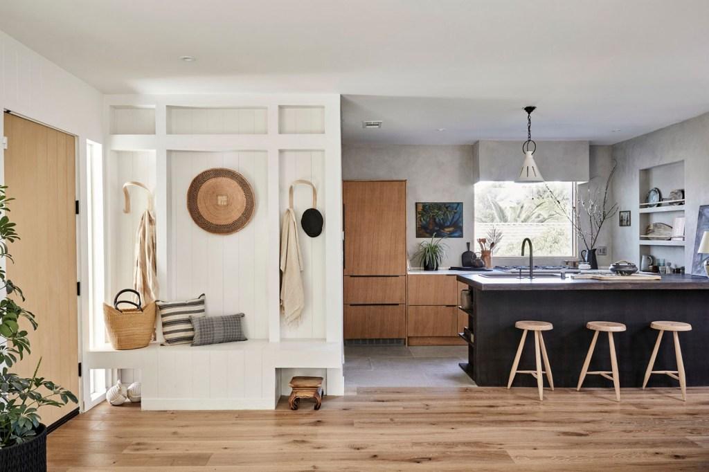 Sala de estar com cozinha integrada. Tons de madeira, branco e preto se mesclam para criar ambiente aconchegante