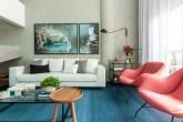 Sala de estar com pé direito alto, cimento queimado na parede, sofá branco e poltronas rosas