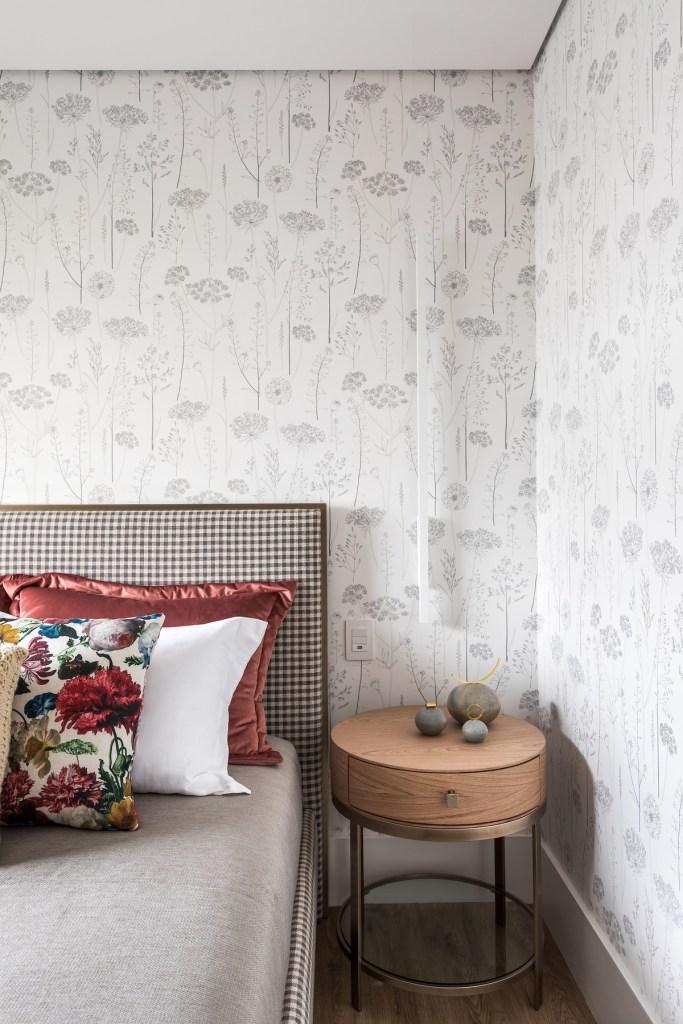 Quarto com papel de parede botânico branco e cinza claro. Almofadas coloridas com estampas floridas