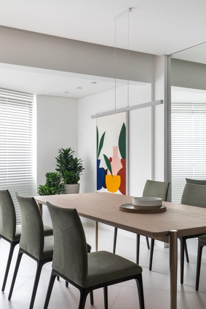 Mesa em madeira com cadeiras verde musgo escuro. Parede espelhada ao fundo. Obra de arte geométrica e colorida junto de folhagens no canto da sala