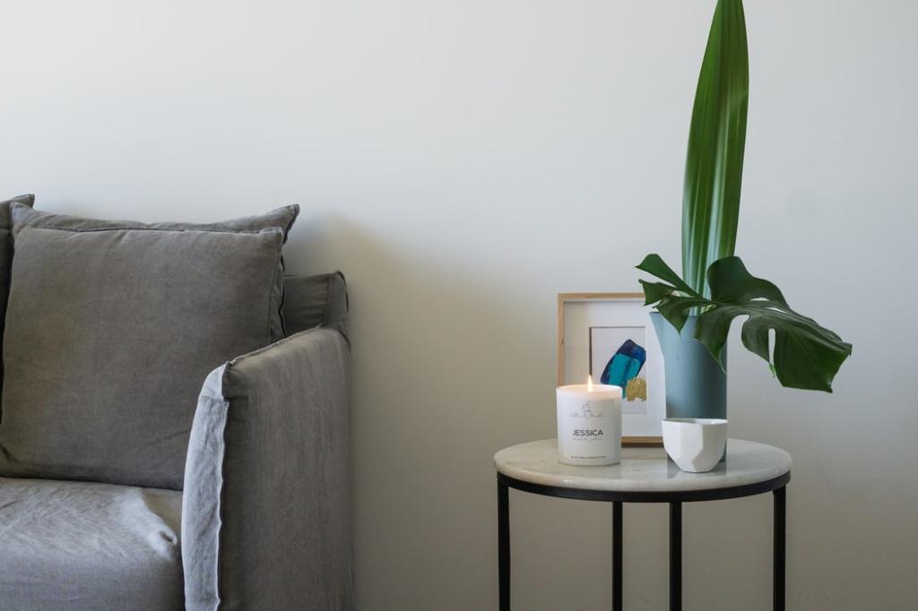 sofá cinza com mesa lateral com pés de metal preto e tampo em pedra branca, com porta retrato, vaso com planta e vela