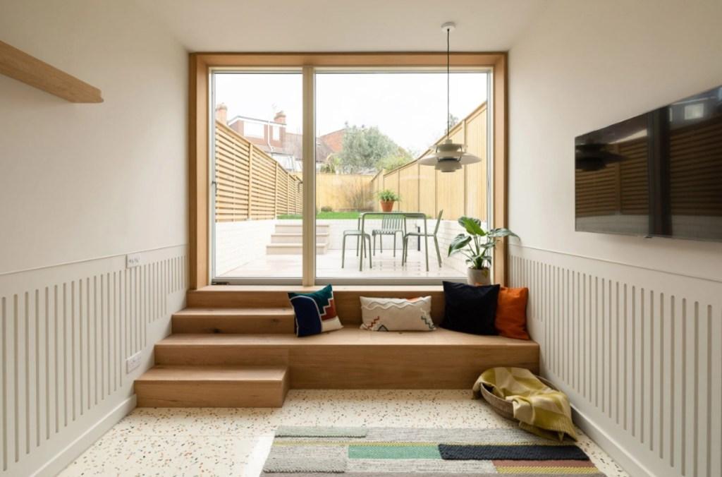 Pequeno estar claro com tv e tapete listrado. Escada de madeira com almofadas leva até porta de vidro que dá para o quintal dos fundos