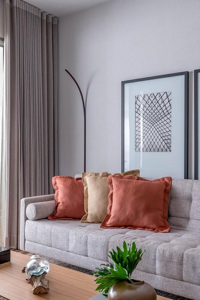 Sala de estar com sofá cinza, com almofadas laranja e amarela com luminária de chão