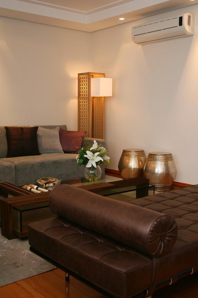 Sala de estar com sofás cinza e de couro marrom, com luminária de chão com cor amarelada