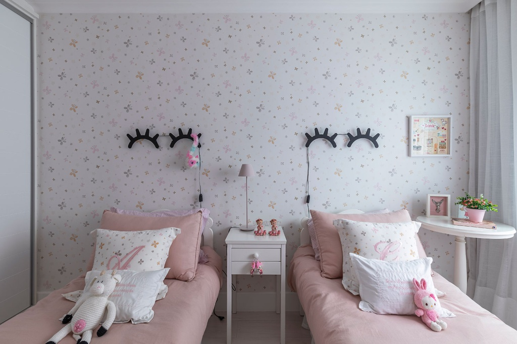 Quarto infantil, com duas camas com roupa rosa e luminárias sobre elas em formato de olhos fechados com cílios