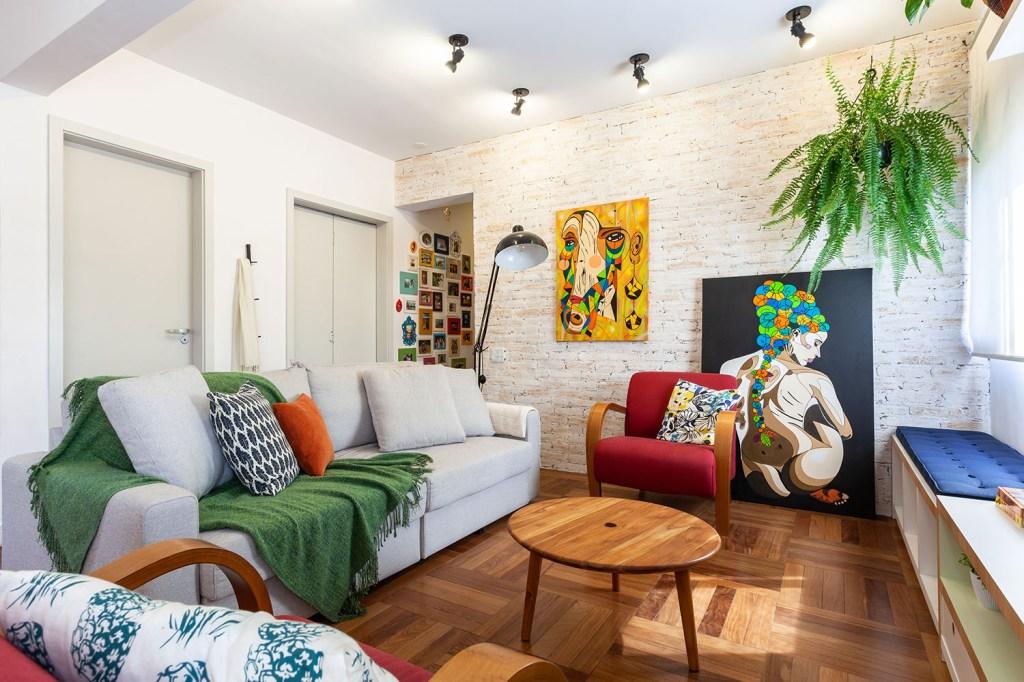 Sala de estar em tons neutro, com detalhes, como manta sobre o sofá, quadros na parede e poltrona coloridos