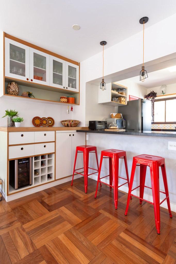 Cozinha em cores neutras, branco e madeira, com banquetas vermelhas