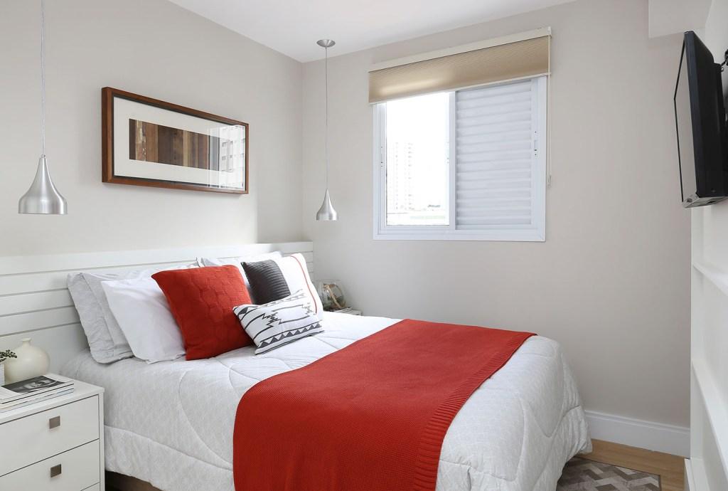 Quarto de casal com cores neutras, mas detalhes, como manta e almofadas sobre a cama, em vermelho
