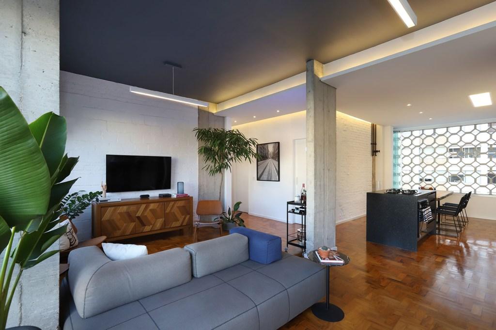 Living integrado com piso de madeira, sofá cinza e teto na mesma cor