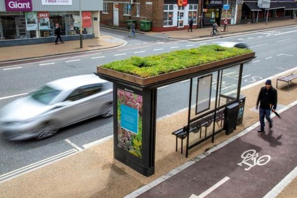 Ponto de ônibus com cobertura verde ao lado de ciclovia
