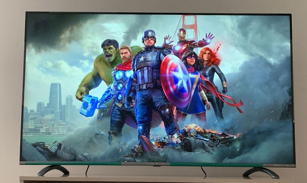 """TV Britânia 55"""" com tela de carregamento do jogo Marvel'Avengers, com personagens do jogo agrupados ao centro"""