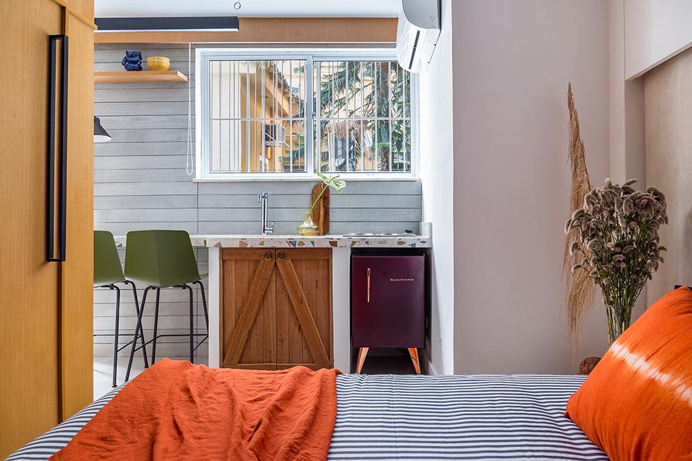 loft com cama de casal. Lençol listrado branco a azul. Travesseiros laranja. Bancada com pia ao fundo. Mini geladeira roxa. Bancos verdes