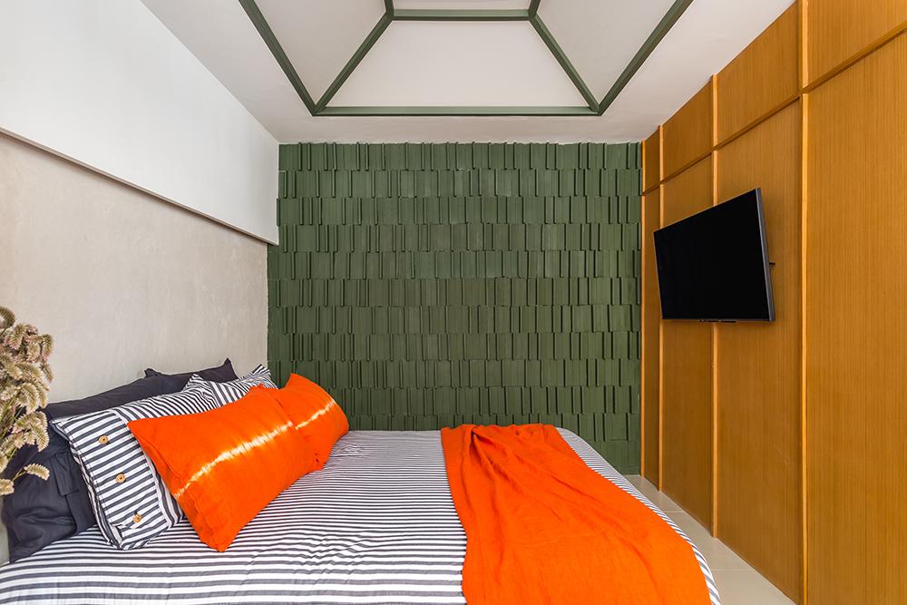 Quarto com cama de casal. Parede revestida de madeira. Parede do fundo com papel de parede 3d texturizado verde escuro. Claraboia no teto